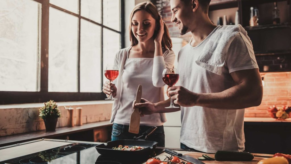 Couples cooking at home with wine in hand